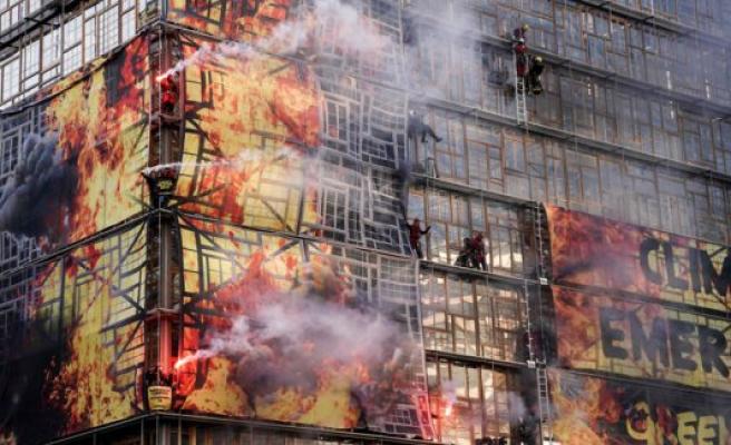 Activists wraps the building in a false flammehav before EU summit